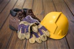 Casque antichoc, gants et bottes fonctionnants jaunes de travail dessus Photos stock
