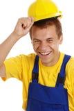 casque antichoc heureux sien outre du sourire prenant l'ouvrier Photographie stock