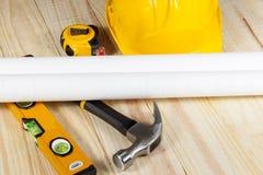 Casque antichoc jaune et plans de situation s'étendant sur un plancher en bois Photographie stock libre de droits