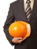 Casque antichoc orange dans la main d'ingénieur ou d'architecte Images libres de droits