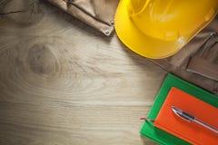 Casque de bâtiment de ceinture d'outil de cuir de stylo de carnets sur le conseil en bois Photo stock
