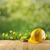 Casque de construction sur le fond vert de nature Photographie stock