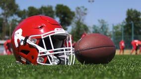 Casque de football et boule sur l'herbe banque de vidéos