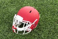 Casque de football rouge sur un champ vert de gazon Photographie stock libre de droits