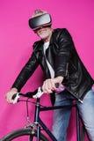 Casque de port élégant de réalité virtuelle d'homme supérieur et bicyclette de monte Photos libres de droits