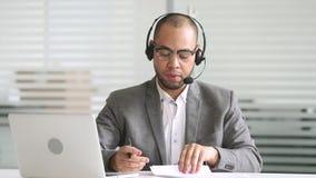 Casque de port d'agent africain sérieux de support à la clientèle parlant avec le client clips vidéos