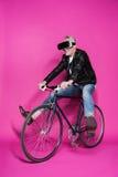 Casque de port de sourire de réalité virtuelle d'homme supérieur et bicyclette de monte Image stock
