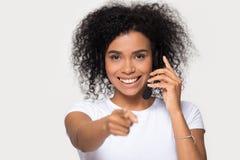 Casque de port de sourire de femme africaine semblant dirigeant le doigt à la caméra photographie stock