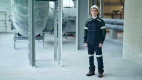 Casque de protection de port de jeune ingénieur posant regardant l'appareil-photo l'usine moderne banque de vidéos