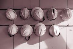 Casque de sécurité accrochant sur le mur dans le ton de sépia pour la construction photographie stock libre de droits
