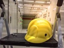 Casque de sécurité jaune dans la chambre électrique située sous le plancher augmenté photographie stock