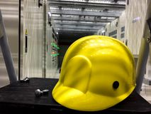 Casque de sécurité jaune dans la chambre électrique située sous le plancher augmenté photos stock