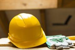 Casque et gants de sécurité jaunes sur la surface de fonctionnement au site de rénovation de grenier photographie stock libre de droits