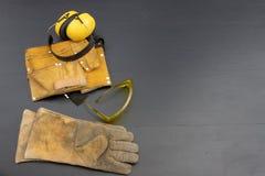 Casque et gants sur un établi noir Habillement de travail pour le constr photographie stock libre de droits