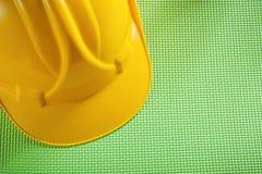 Casque jaune de bâtiment sur le concept vert de construction de fond Images libres de droits