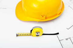Casque jaune de construction avec la bande de mesure près de elle Photos stock