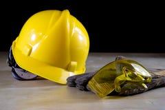 Casque, lunettes de sécurité et gants jaunes de travail pour le travailleur dessus image stock