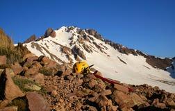 Casque s'élevant jaune et hache de glace rouge, se trouvant sur une roche dans les montagnes Images stock