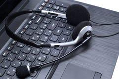 Casque se trouvant sur un clavier d'ordinateur portable Photos stock