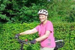 Casque supérieur de bicyclette de femme dehors Images stock