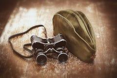 Casquillo de campo del soldado, prismáticos militares Fotografía de archivo