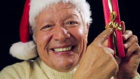 Casquillo de Jolly Old Man With Santa que señala en el regalo rojo almacen de video