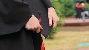 Casquillo de la graduación con la borla roja en las manos del estudiante, logro, futuro almacen de metraje de vídeo