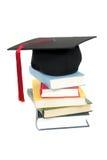 Casquillo de la graduación en la pila de libros Fotografía de archivo