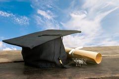 casquillo de la graduación, sombrero con el documento del grado sobre la tabla de madera, backgro del cielo Fotografía de archivo libre de regalías