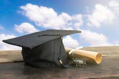 casquillo de la graduación, sombrero con el documento del grado sobre la tabla de madera, backgro del cielo Imagen de archivo libre de regalías