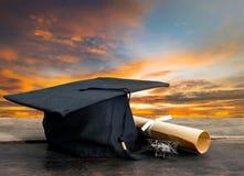 casquillo de la graduación, sombrero con el documento del grado sobre la tabla de madera, cielo de la puesta del sol Foto de archivo