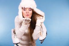 Casquillo de la piel de la mujer que lleva que sostiene patines de hielo foto de archivo libre de regalías