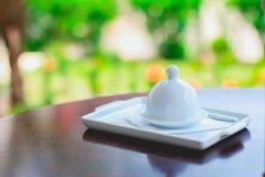 Casquillo del plato de porcelana en una tabla de madera fotografía de archivo
