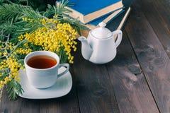 Casquillo del té y libro en la sobremesa imagenes de archivo