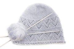 Casquillo hecho punto de lana gris con el ovillo y las agujas Imágenes de archivo libres de regalías
