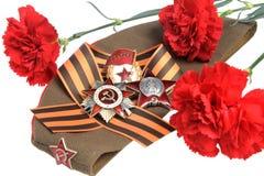 Casquillo militar con las flores rojas, cinta de San Jorge, órdenes de la gran guerra patriótica Imagen de archivo libre de regalías
