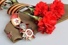 Casquillo militar, flores rojas, cinta de San Jorge, órdenes de la gran guerra patriótica Imagen de archivo