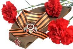 Casquillo militar, orden de la gran guerra patriótica, flores, cinta de San Jorge Fotos de archivo