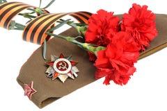 Casquillo militar, orden de la gran guerra patriótica, flores rojas, cinta de San Jorge Imagenes de archivo
