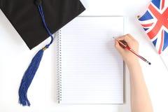 Casquillo negro de la graduación con el cuaderno foto de archivo libre de regalías