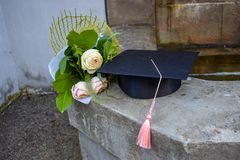 Casquillo o mortaboard de la graduación con un manojo de rosas en las escaleras viejas en el día de graduación foto de archivo