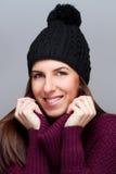 Casquillo que lleva de la mujer feliz y sonrisa en fondo ligero Foto de archivo libre de regalías