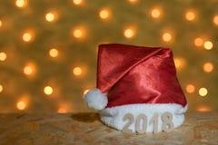 Casquillo rojo con las figuras de 2018 en una tabla en el fondo de una guirnalda del ` s del Año Nuevo con las luces de oro borro Fotografía de archivo libre de regalías
