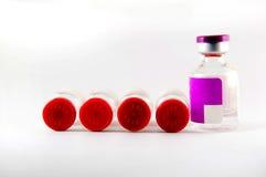 Casquillo rojo y frascos púrpuras de la inyección de la etiqueta Foto de archivo libre de regalías