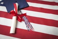 Casquillo y diploma de la graduación que descansan sobre bandera americana Fotografía de archivo