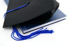 Casquillo y libro de la graduación Fotos de archivo