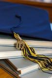 Casquillo y libros de la graduación foto de archivo
