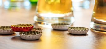 Casquillos de la cerveza y vidrios de cerveza en un fondo del pub Imagen de archivo libre de regalías