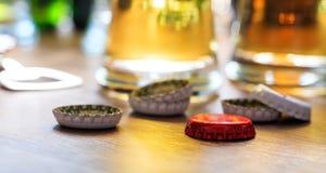 Casquillos de la cerveza y vidrios de cerveza en un fondo del pub Fotografía de archivo libre de regalías