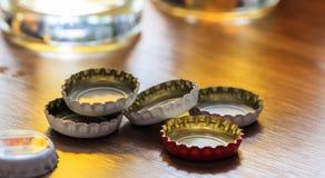 Casquillos de la cerveza y vidrios de cerveza en un fondo del pub Fotos de archivo libres de regalías
